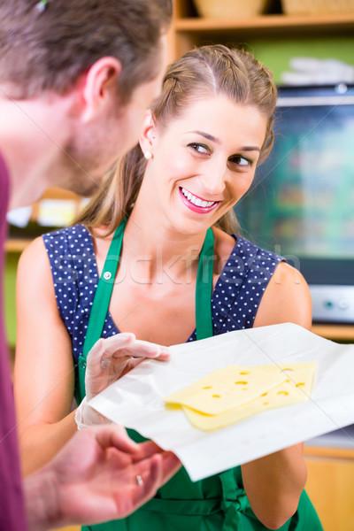 Saleswoman at counter offering cheese Stock photo © Kzenon