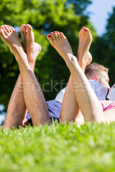 Friends laying  with crossed legs in park Stock photo © Kzenon