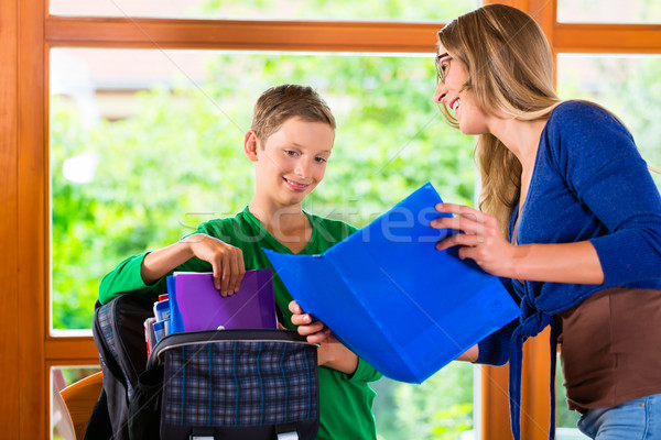 Mother and son packing school bag Stock photo © Kzenon