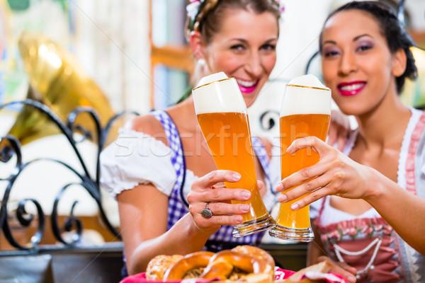 Women in Bavarian pub toasting with wheat beer Stock photo © Kzenon