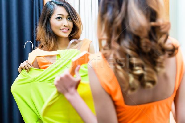 Asian woman choosing dress in store fitting room  Stock photo © Kzenon