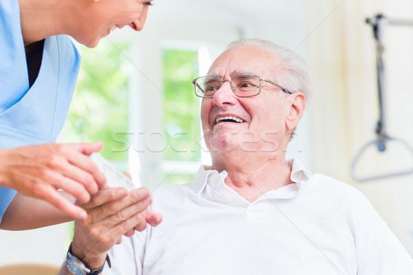 Nurse giving senior man prescription drugs Stock photo © Kzenon