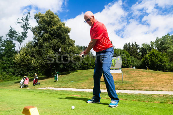 Senior man doing tee stroke on golf course Stock photo © Kzenon