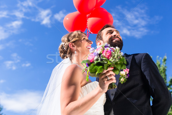 Bride and groom at wedding with read helium balloons Stock photo © Kzenon