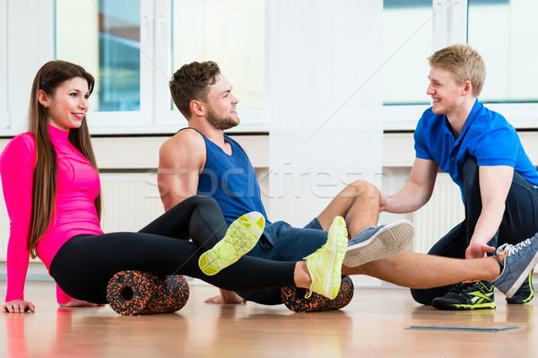 Physio of health club explaining exercises with roll  Stock photo © Kzenon