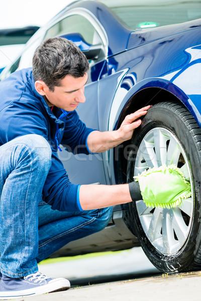 Worker using microfiber car wash mitt for cleaning rim  Stock photo © Kzenon