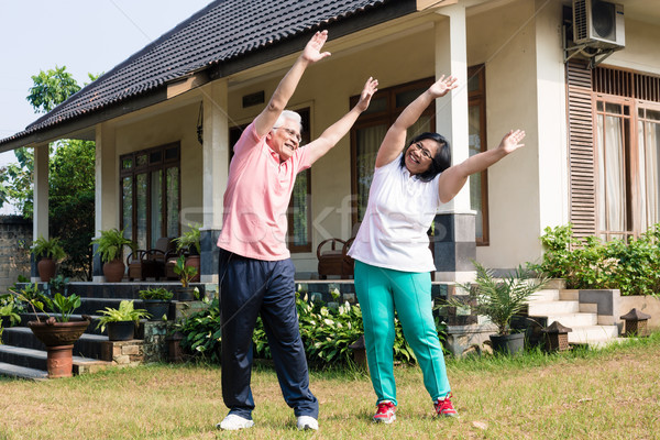 Active senior couple exercising with raised arms outdoors Stock photo © Kzenon