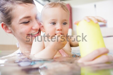 Baby learning to crawl in mother and child gymnastic course Stock photo © Kzenon