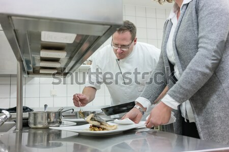 Chef finishing fish on plate in restaurant Stock photo © Kzenon