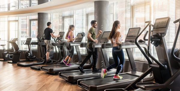 Stock photo: Group of four people running on treadmills in fitness gym