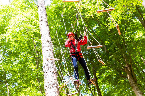 Child reaching platform climbing in high rope course Stock photo © Kzenon