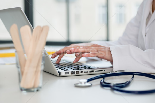 Close-up of the hands of a physician typing on laptop in the off Stock photo © Kzenon