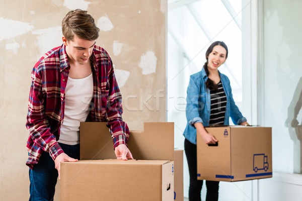 Young man opening a box while moving in with his girlfriend Stock photo © Kzenon