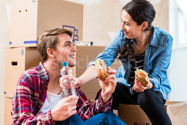 Young couple looking tired while eating a sandwich during renovation Stock photo © Kzenon
