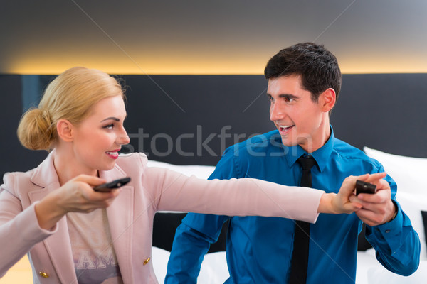 Couple switching TV with remote control in hotel room Stock photo © Kzenon