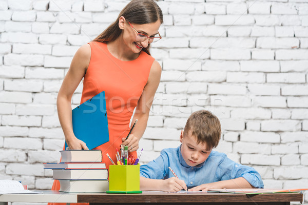 Teacher helping student with difficult task in school  Stock photo © Kzenon