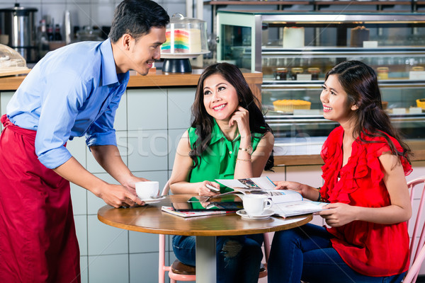 Handsome waiter serving coffee at the table of two beautiful women Stock photo © Kzenon