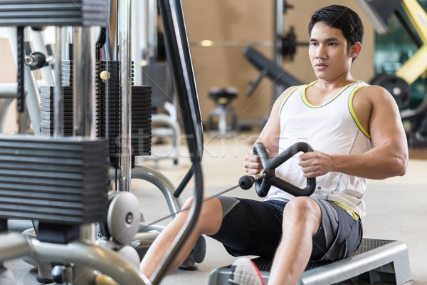 Determined young man looking forward while rowing at the cable machine Stock photo © Kzenon