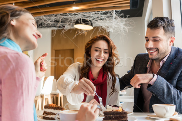 Three friends smiling while eating delicious cakes in their cheat day Stock photo © Kzenon