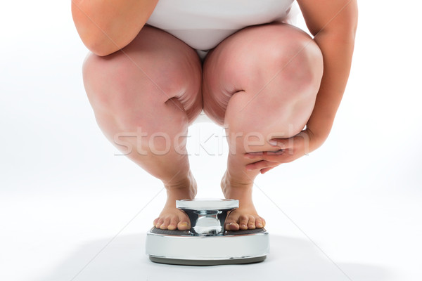 Obese young woman crouching on a scale Stock photo © Kzenon
