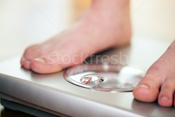 Woman standing on bathroom scale Stock photo © Kzenon