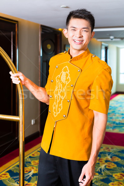 Asian bell boy or porter bringing suitcase to hotel room Stock photo © Kzenon