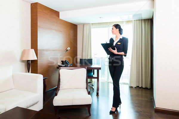Asian executive housekeeper controlling hotel room Stock photo © Kzenon