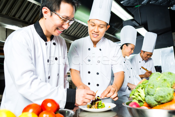 Asian Chef in restaurant kitchen cooking Stock photo © Kzenon