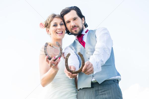 Wedding couple showing horse shoe for luck Stock photo © Kzenon