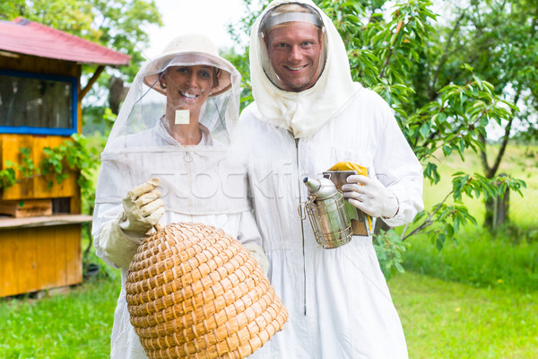Beekeeper team working outdoor with smoker and beehive   Stock photo © Kzenon