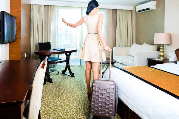 Rear view of woman pulling suitcase in hotel room Stock photo © Kzenon