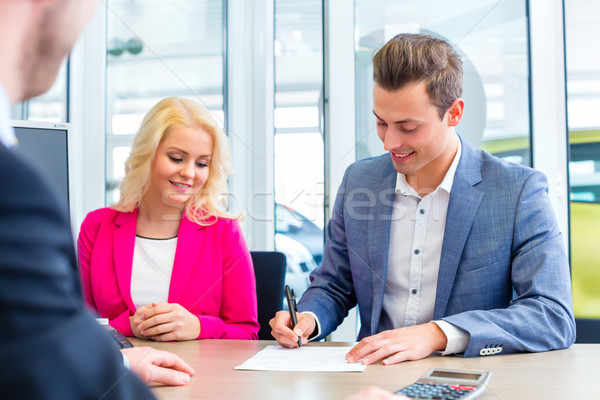 Man signing sales contract for auto at car dealership  Stock photo © Kzenon