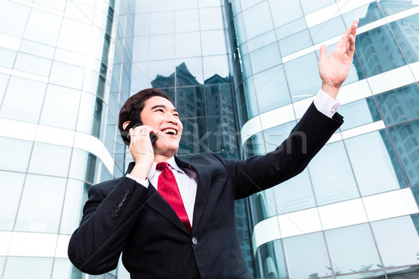 Stock photo: Asian business man talking outside to mobile phone