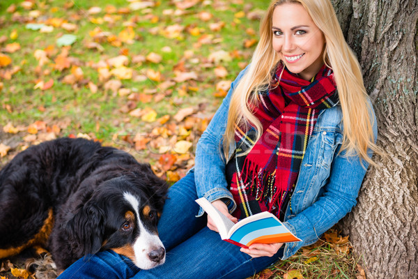 Stock photo: Woman with dog reading book in autumn park