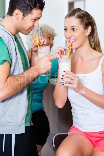 People drinking protein shakes in fitness gym Stock photo © Kzenon