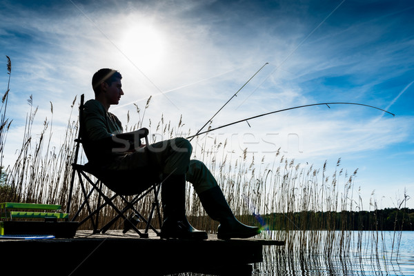Fisherman or Angler at lake in Sunrise backlit Stock photo © Kzenon
