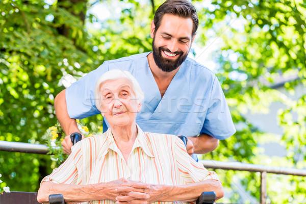 Geriatric nurse giving senior woman massage Stock photo © Kzenon