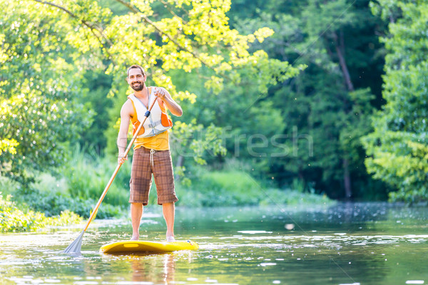 Man paddling on SUP in river Stock photo © Kzenon