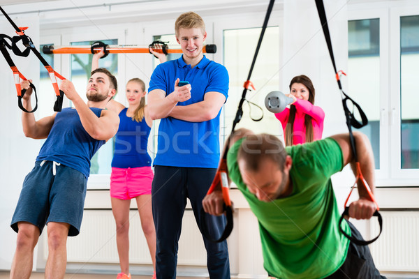 Athletes at gym during ring gymnastics with their personal train Stock photo © Kzenon
