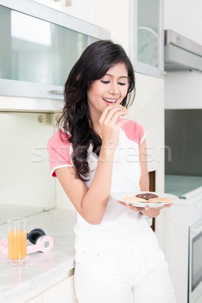 Indonéz nő eszik sütik konyha Stock fotó © Kzenon