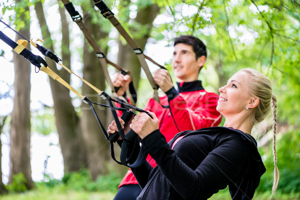 Sporty couple at sling trainer doing fitness Stock photo © Kzenon