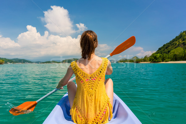 Young woman paddling a canoe during vacation in Flores Island, Indonesia Stock photo © Kzenon