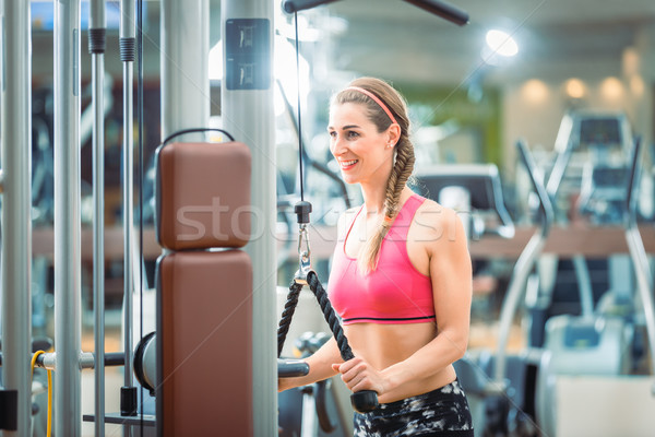 Happy fit woman wearing pink fitness bra while exercising Stock photo © Kzenon