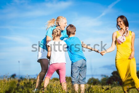 Family in playful mode on a meadow in summer Stock photo © Kzenon