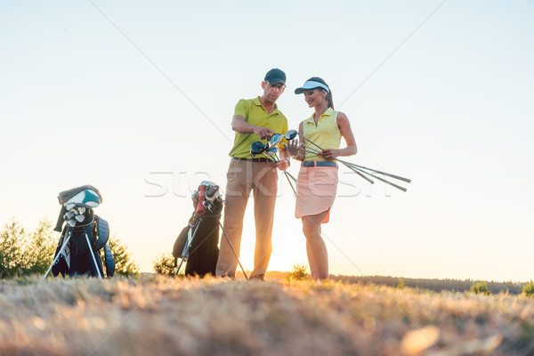 Golf instructor teaching a young woman how to use different golf clubs Stock photo © Kzenon