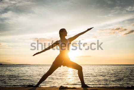 Silhouette of a fit woman practicing the warrior yoga pose against sunset Stock photo © Kzenon