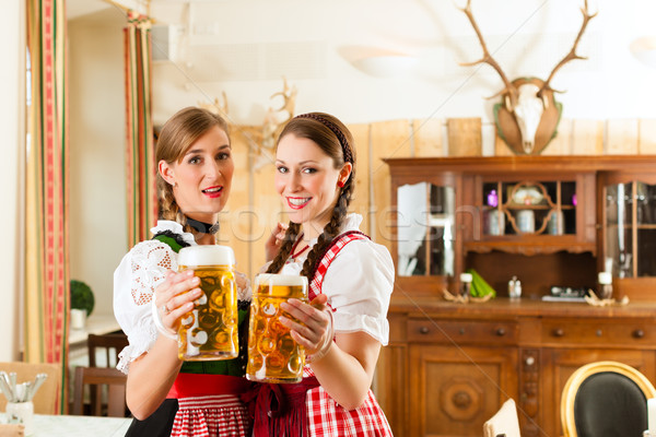 Two young women in traditional Bavarian Tracht in restaurant or pub Stock photo © Kzenon