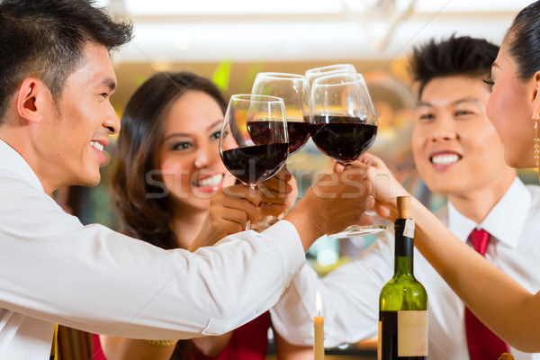 Stock photo: Chinese couples toasting with wine in restaurant