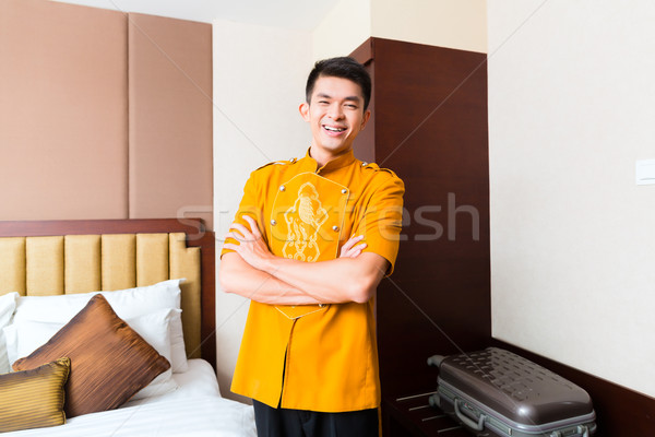 Asian Chinese porter bringing suitcase to luxury hotel room Stock photo © Kzenon
