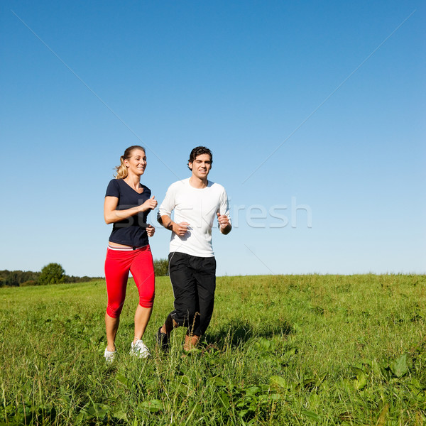 sport couple jogging an meadow in summer Stock photo © Kzenon